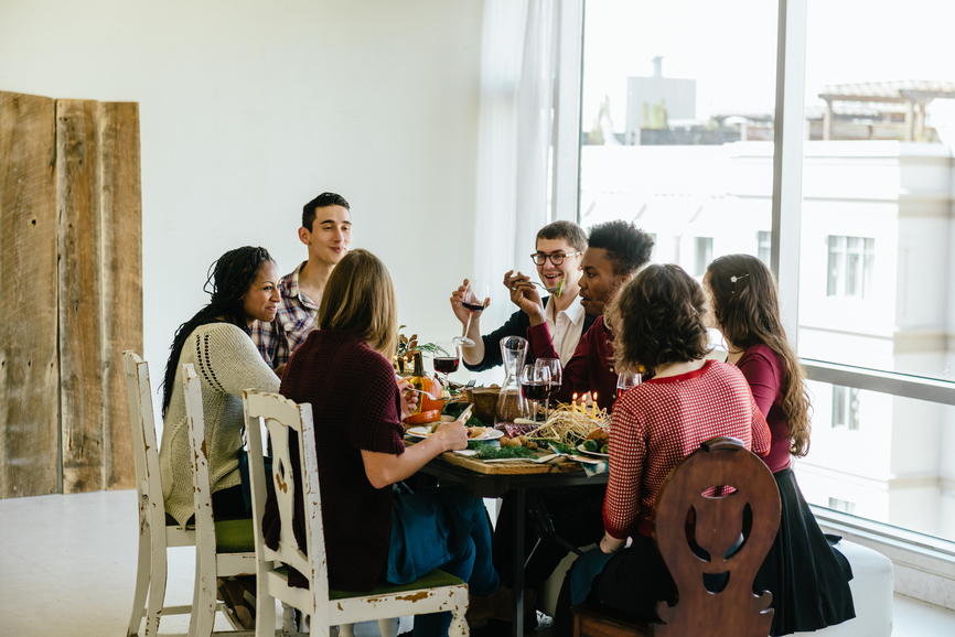 A group of friends eating Thanksgiving dinner together.