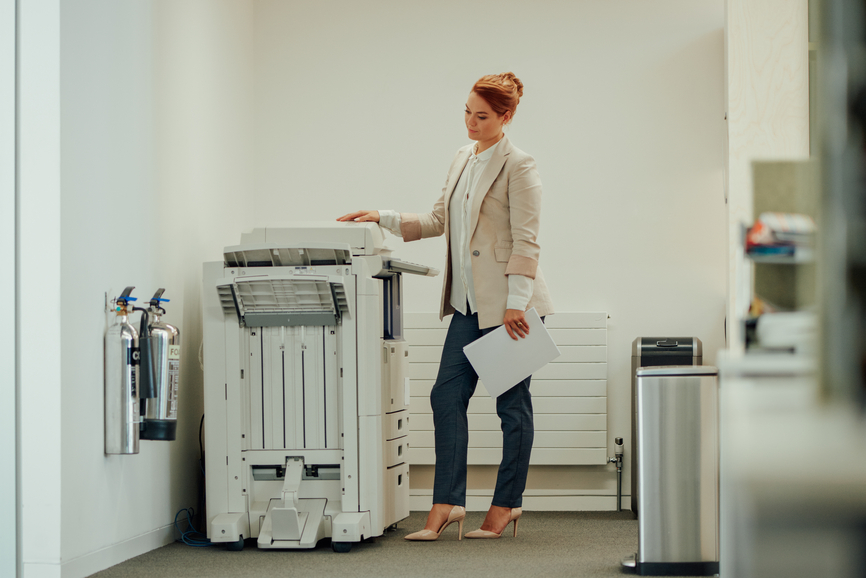 Full length profile view of young modern businesswoman wearing jeans & jacket standing waiting at photocopier close to file room doorway