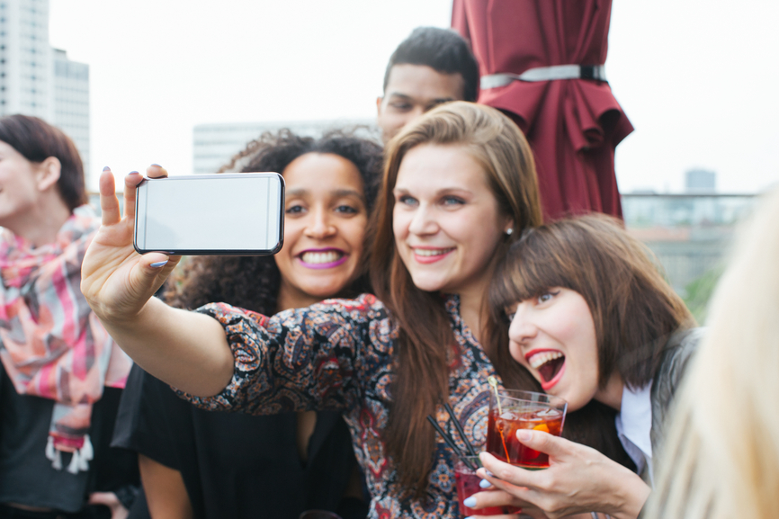 Three Young Women Taking Smartphone Selfie at Rooftop Bar