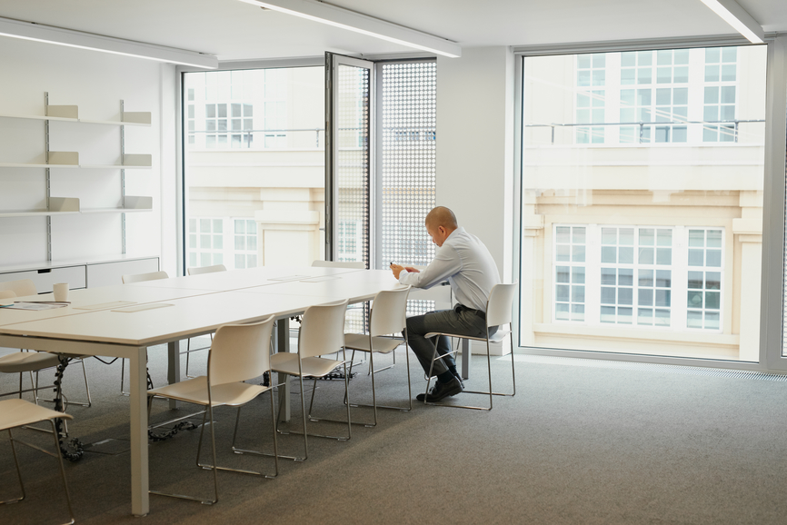 Businessman working alone in boardroom after hours on weekend