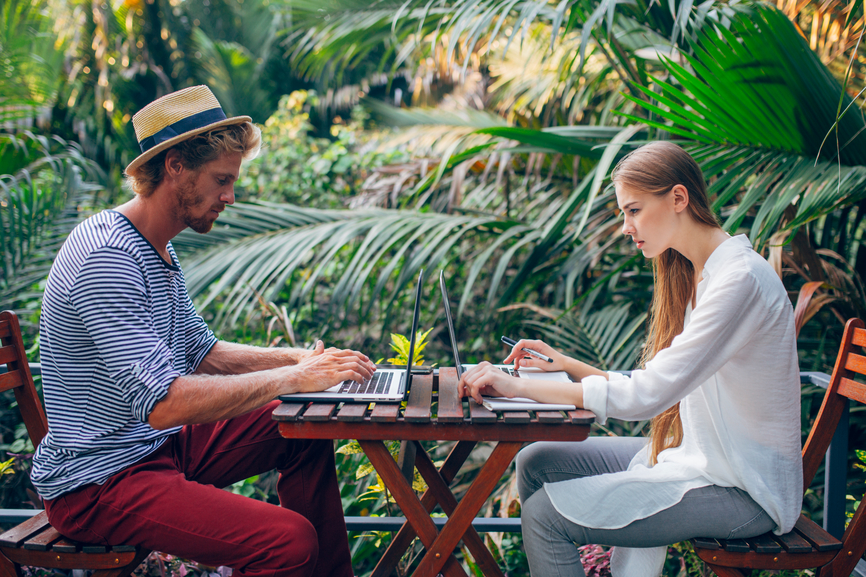 Couple working on a terrace on vacation in a tropical area.